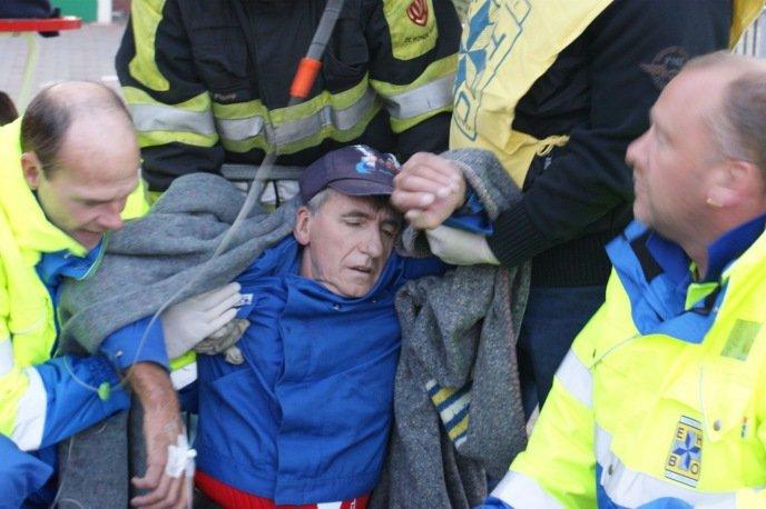 Slachtoffer in shock wordt op brancard geholpen