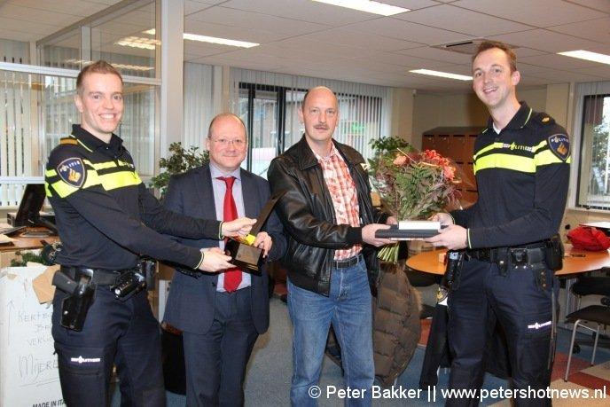 Martien van Herk (rechts) overhandigt Rob Voorbij een presentje en bloemen voor zijn inzet. Terwijl burgemeester Divendal de speciale trofee in ontvangst neemt van Peter Smit (links)