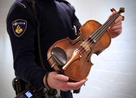 Een politieagent met de in Abcoude gestolen viool - een Randolfi uit 1731 -