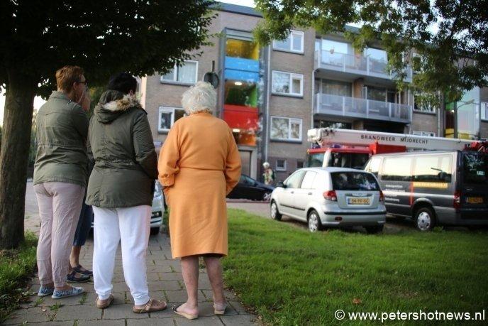 Bewoners staan buiten te wachten tot ze weer naar huis mogen. Even later werd de naastgelegen school open gesteld.